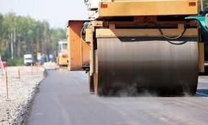 Machines paving down asphalt on a naples florida roadway.