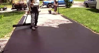 applying sealcoat mixture on top of older driveway