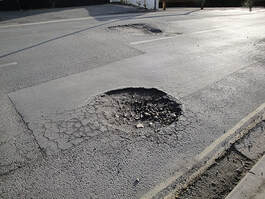 a roadway pothole that needs repaired